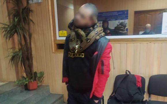 П'яний чоловік зі зміями на шиї чіплявся до людей у Києві. ФОТО